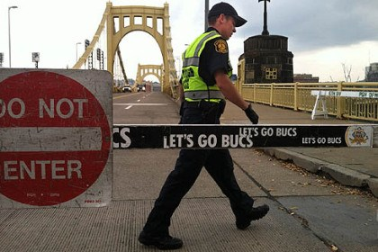 The bridge is closed Pittsburgh police officer W. Mudron pulls baracades this morning to block the Clemente Bridge for the Pirates watch party.
