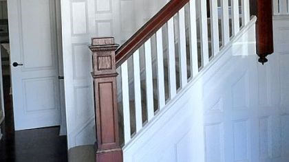 The entryway In the large entryway, the wood was was stripped, the paneling was painted white, and the rails and banisters were restored to a deep cherry.