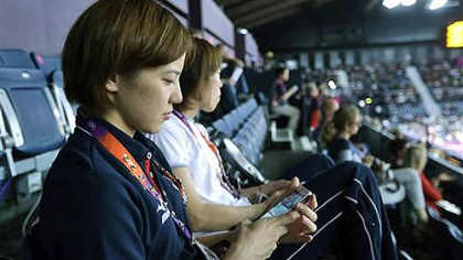The Twitter Factor Japan's Miyuki Maeda checks at her iPhone as she watches badminton matches in progress at the Summer Olympics, Tuesday, July 31, 2012, in London. The 2012 games are being shaped, shaken and indisputably changed by the social media revolution.