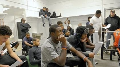 Titus Howard, Titus Howard, center, a junior wide receiver and cornerback who has made a verbal commitment to play football at the University of Pittsburgh, and his Bears teammates listen to defensive coach Wayne Wade during a recent strategy session in the team's weight room.