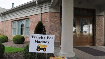 trucks out front A dump truck is left at the entrance of the Slater Funeral Home in Scott on Thursday in honor of Maddox Derkosh.