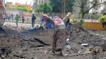 Turkey A woman raises her arms and shouts Saturday as she stands at the site where two car bombs exploded near the town hall in Reyhanli, Turkey, which is close to the Syrian border. The blasts killed 43 people and injured 140.