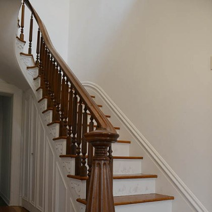 Upon entering the 17- by 7-foot foyer Upon entering the 17- by 7-foot foyer, the visitor notices a grand staircase and hardwood floors that run throughout the house.