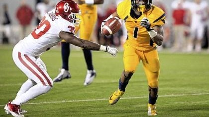 West Virginia West Virginia wide receiver Tavon Austin (1) slips past Oklahoma's Javon Harris (30) for a rushing touchdown Saturday in Morgantown, W.Va.