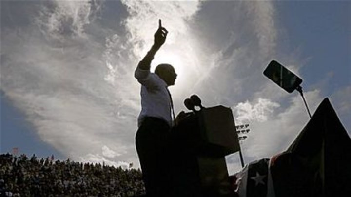 A silhouetted President Barack Obama A silhouetted President Barack Obama gestures while speaking at a campaign event at Delray Beach Tennis Center, in Delray Beach, Fla.,