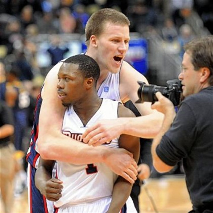 abele Duquesne's Martins Abele, rear, hugs teammate Derrick Colter Tuesday after the Dukes rallied to beat West Virginia, 60-56, at Consol Energy Center.