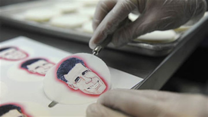 Alan Phillips Alan Phillips applies edible paper with caricatures of the presidential candidates to shortbread cookies at Bethel Bakery in Bethel Park on Wednesday.