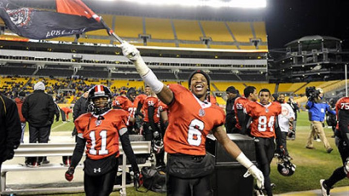 Aliquippa's Dravon Henry Aliquippa's Dravon Henry waves his school's flag after defeating Washington Friday in the WPIAL class AA championships at Heinz Field.