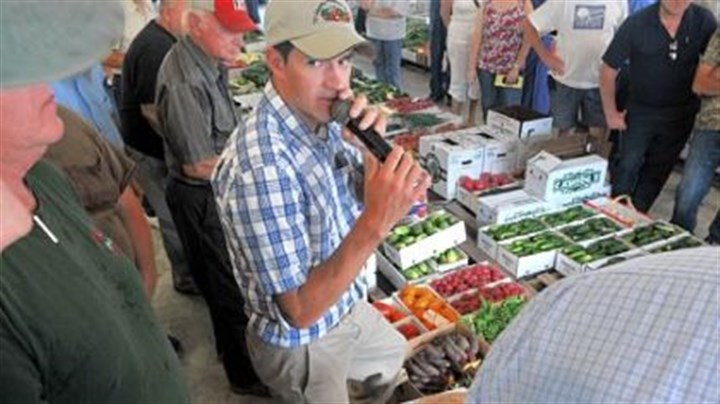 Auctioneer Andrew Yoder Auctioneer Andrew Yoder watches for a higher bid on a box of beets as he deals with the merchandise at the Tri County Produce Auction.