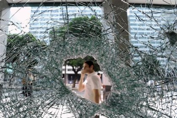 Brazil Pedestrians pass by a bank Saturday with its windows broken during an overnight protest in downtown Rio de Janeiro, Brazil.