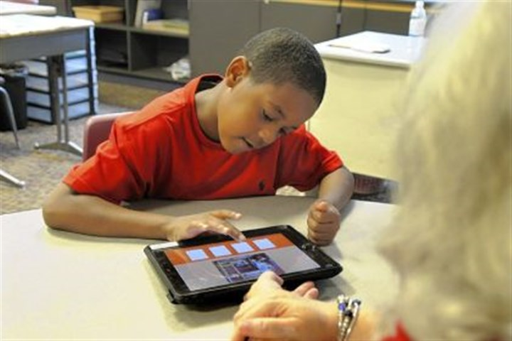 Breaking Down Barriers Marlene Berncic helps a student work on an iPad during a second- to fourth-grade class at Pace school in Churchill.