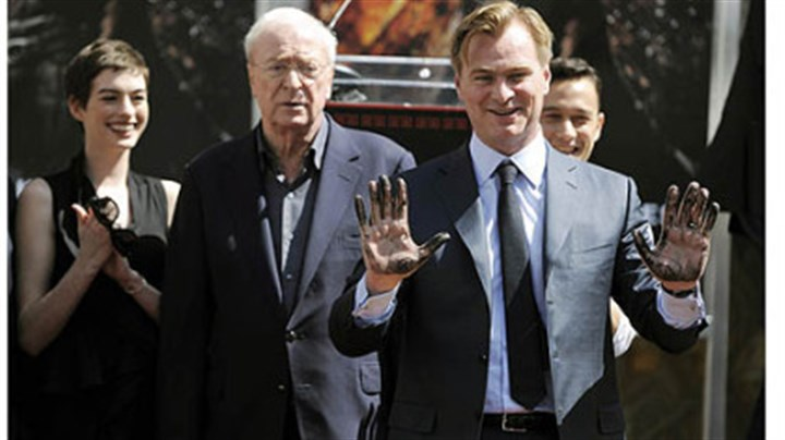 "Christopher Nolan and cast Christopher Nolan director of the film ""The Dark Knight Rises,"" holds up his hands after putting them in cement during a ceremony for him at Grauman's Chinese Theatre."