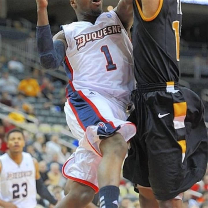 Colter Duquesne's Derrick Colter drives to the basket against VCU's Darius Theus. Colter paced the Dukes with 15 points.