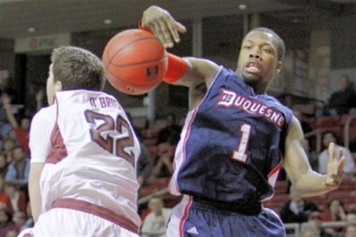 Colter Duquesne's Derrick Colter knocks a rebound away from Temple's Jake O'Brien in the second half Thursday in Philadelphia. Duquesne earned its first Atlantic 10 win of the year, 84-83.