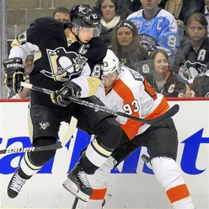 Crosby The Penguins' Sidney Crosby works the pucks along the boards against the Flyers' Jakub Voracek in a game against Philadelphia earlier this season.