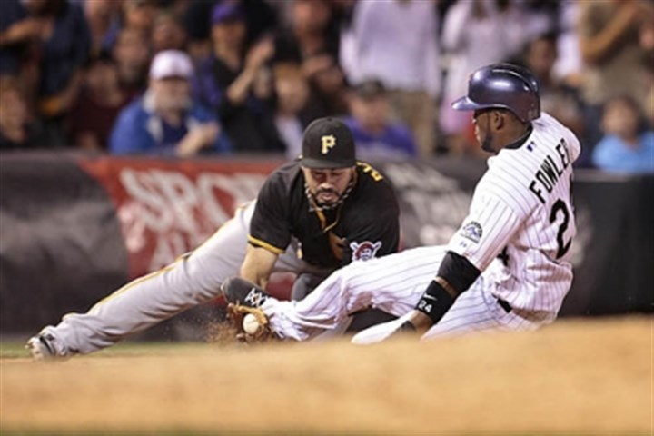 Dexter Fowler and Pedro Alvarez The Rockies' Dexter Fowler, right, knocks the ball loose as he slides into the Pirates' Pedro Alvarez at third base in the sixth inning Sunday. Fowler scored on the play.