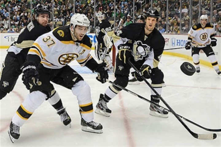 EatonNiskanen Penguins defensemen Mark Eaton, right, and Matt Niskanen, left, tie up the Bruins' Patrice Bergeron.