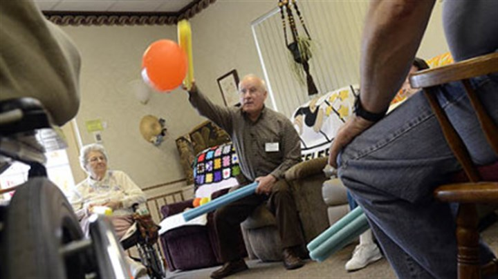 Exercise activity Alan Romatowski takes part in an exercise with other patients at Concordia Adult Day Services, using foam sticks to bat away balloons.