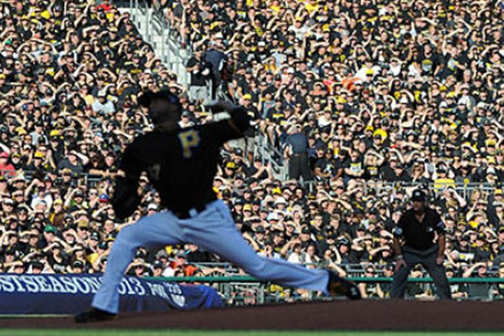 "Francisco Liriano Pirates pitcher Francisco Liriano pitches in the first inning against a background of fans dressed in black. Fans were asked to ""Black Out"" the stands for today's game."