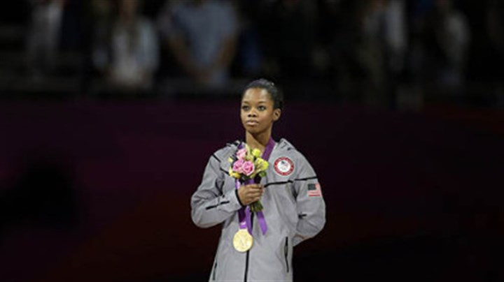Gabrielle Douglas with gold medal The 16-year-old from Virginia Beach, Va., the first African-American to win the individual gold in the event, displays her medal below.