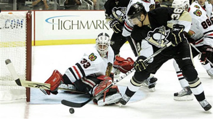 Hannu Toivonen and Nick Johnson Blackhawks goaltender Hannu Toivonen makes a save against Penguins forward Nick Johnson.