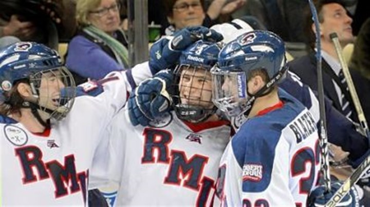 hinds Robert Morris' Tyler Hinds, middle, is congratulated after scoring in the third period against Penn State in the Three Rivers Classic Friday at Consol Energy Center.
