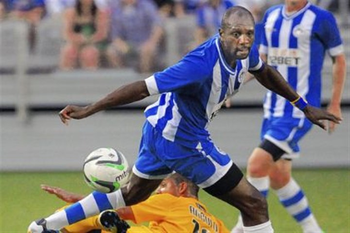 hounds1 Wigan defender Emmerson Boyce has the ball taken away from under him by Riverhounds forward Joe Angulo in the first half Friday at Highmark Stadium. Wigan won, 4-1.