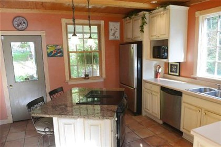 In the kitchen, antique glazed cabinets with a slightly distressed finish In the kitchen, antique glazed cabinets with a slightly distressed finish include a floor-to-ceiling pantry and a built-in microwave shelf. Stainless-steel appliances include a Maytag dishwasher and Jenn-Air refrigerator and stove.