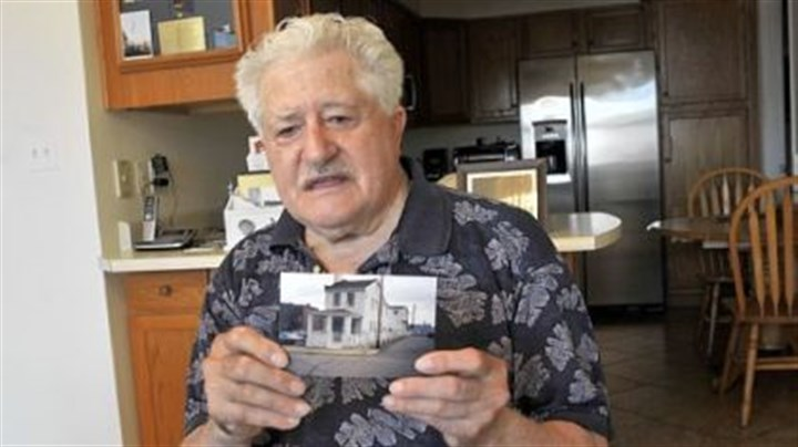 "James Roberto James Roberto, 88, holds a photo of the ""little white house"" he lived in on Marion Street in Uptown for more than 40 years before he sold it to UPMC Mercy. Mr. Roberto, who had rejected several offers from Mercy Hospital, sold the property to UPMC for $573,847."