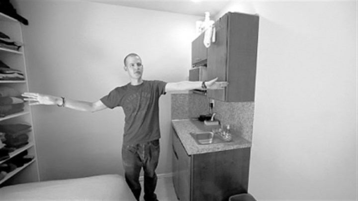 king Seattle resident Kris King spreads his arms as he shows off his tiny apartment.