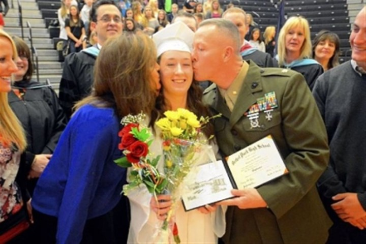 Kiss Bethel Park High School senior Melanie Burchfield gets a kiss from her father and stepmother, Maj. Jim Burchfield and Patti Burchfield, during a mock graduation ceremony Wednesday at the school.