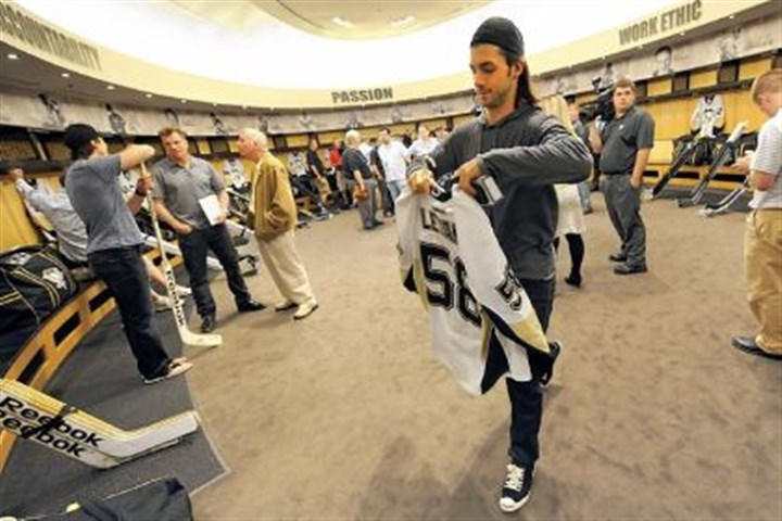 Kris Letang Kris Letang holds his jersey as his teammates clean out their lockers for the season Sunday at Consol Energy Center.
