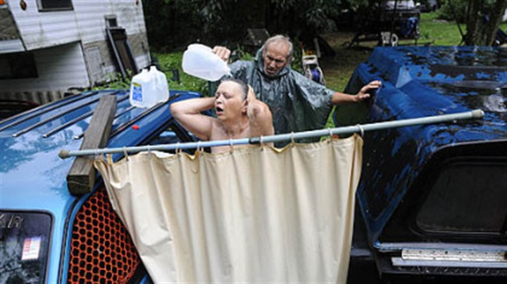 Makeshift shower Fred McIntyre, 56, helps his wife Janet, 52, shower during a heavy rainstorm July 19. The McIntyres usually drive 11 miles to their son's home to shower but when the weather is nice, they will set up a makeshift shower in their front yard in the Woodlands.