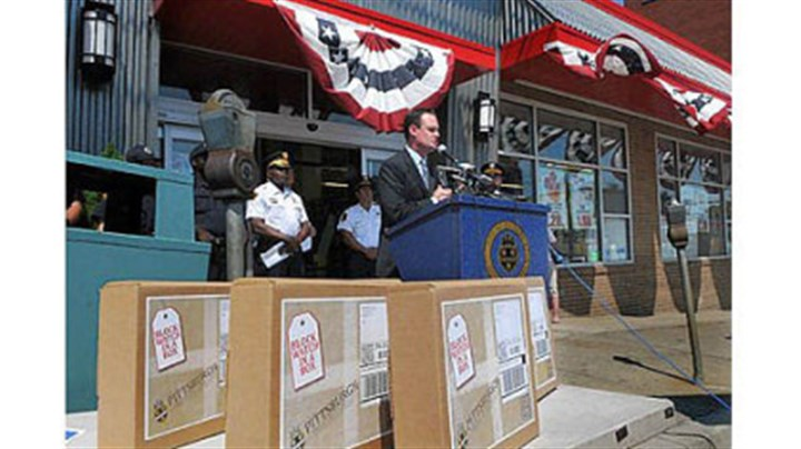 "Mayor Luke Ravenstahl Mayor Luke Ravenstahl speaks in front of the IGA in Beechview, with ""Block Watch in a Box"" boxes in the foreground."