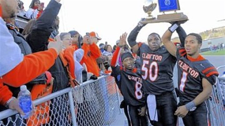moody Clairton teammates (left to right) Vinny Moody, Devonte Harvey and Tyus Booker hold up their trophy after their team's win against Dunmore in the PIAA Class A championship Friday at Hersheypark Stadium in Hershey, Pa.