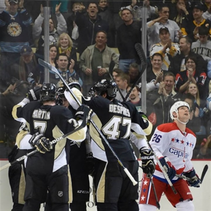 PaulMartin Teammates mob Paul Martin (7) after his second-period goal Tuesday against the Capitals. The Penguins won, 2-1, for their 10th victory in a row.