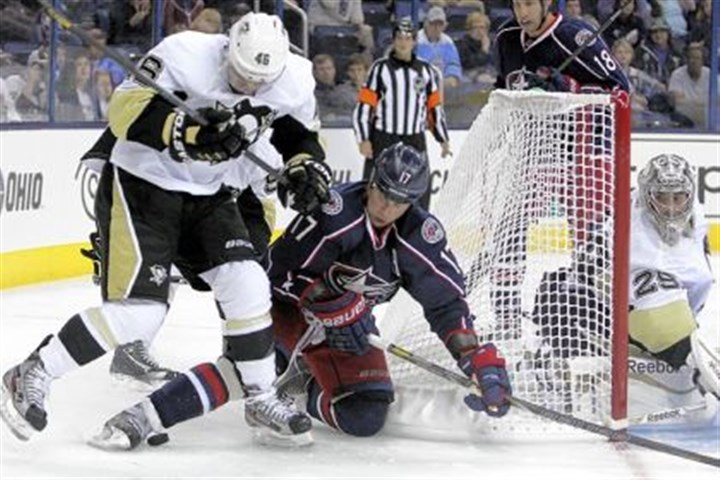 Penguins-1 Penguins goalie Marc-Andre Fleury, right, protects the net as teammate Joe Vitale, left, and the Blue Jackets' Brandon Dubinsky fight for a loose puck in the second period Sunday in Columbus.