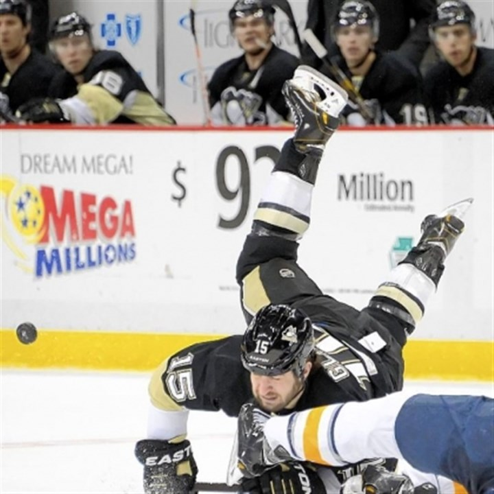 penns2 Tanner Glass tumbles over Buffalo's Mike Weber in the third period at Consol Energy Center.