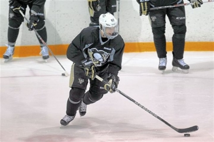 Pens1 Sidney Crosby, in full head-gear, Friday at the Southpointe Iceoplex during his first team practice since his jaw injury in March.