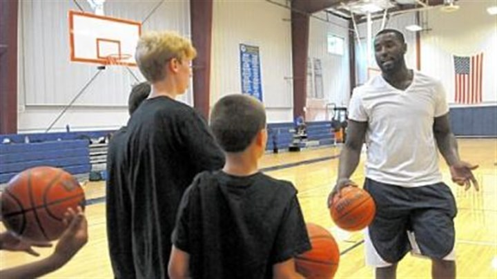 Pitt DeJuan Blair of the NBA San Antonino Spurs explains a drill for campers at his basketball day camp at Aquinas Academy in Hampton.