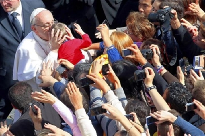 Pope Francis kisses a child Pope Francis kisses a child as he greets the faithful after celebrating Palm Sunday Mass. The pope's first Holy Week will also incorporate him washing the feet of prisoners in a youth detention center in Rome on Thursday.