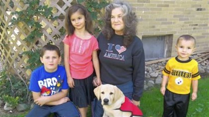 Puppy Rebecca Rodock of Penn Township is raising Remi to become a service dog. With them, from left, are her grandson, Chad Beckett, and great-grandchildren Kaylee and Silas Beckett.