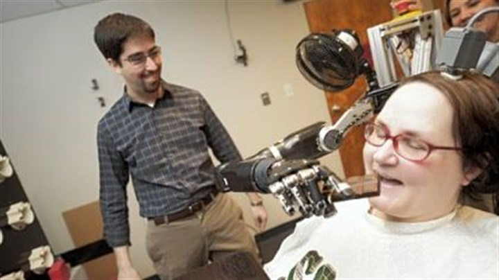 Robot arm Jan Scheuermann, who has quadriplegia, takes a bite from a chocolate bar she has guided into her mouth with a thought-controlled robot arm. Research assistants Brian Wodlinger and Dr. Elke Brown watch.