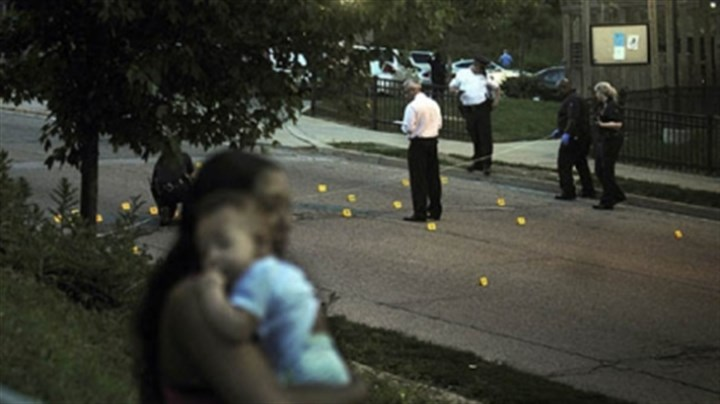Shooting-1 East Hills neighbors watch as Pittsburgh Police and homicide detectives investigate the shooting of two women and a baby.