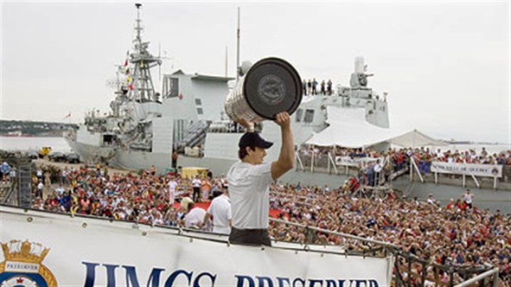Sidney Crosby Penguins captain Sidney Crosby holds up the Stanley Cup on the Canadian navy supply ship HMCS Preserver after a flight on a Sea King helicopter in Halifax, Nova Scotia yesterday.