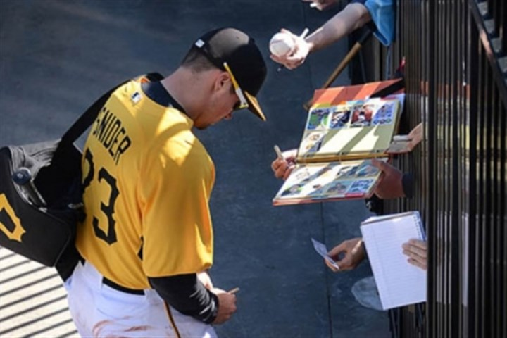 Snider Fans reach through the fence to get autographs from Travis Snider Friday in Bradenton, Fla.