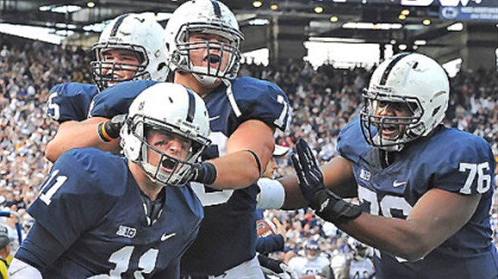 Teammates salute the win Penn State quarterback Matt McGloin is congratulated by teammates after he scored the game-winning touchdown against Northwestern this afternoon at Beaver Stadium in State College.