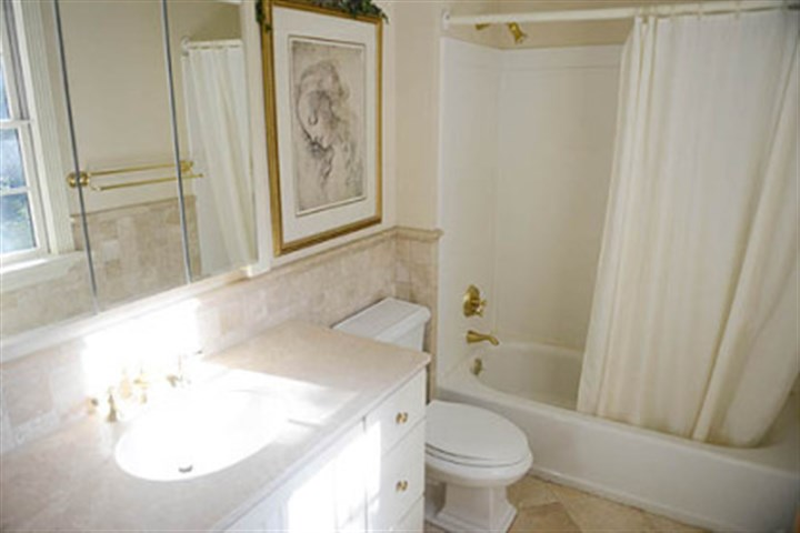 The upstairs bathroom The upstairs bathroom features ceramic tile on the wall and floor and a newer vanity.