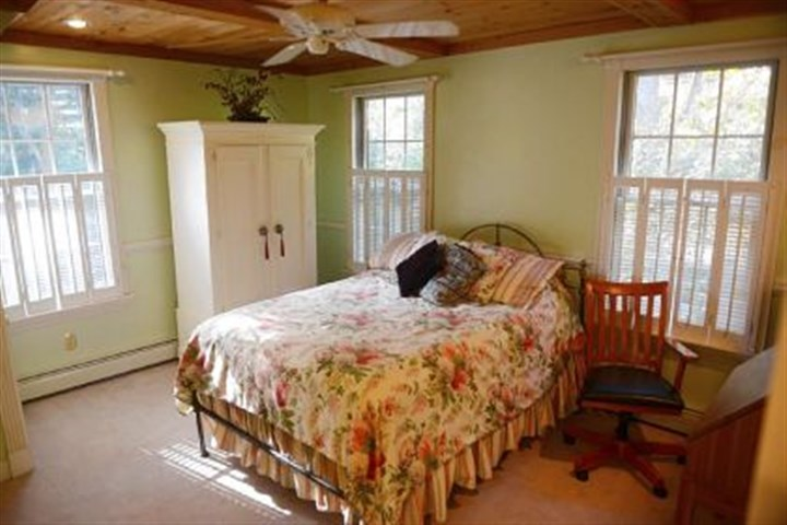This bedroom has white shutters This bedroom has white shutters instead of traditional curtains and features pine ceilings.