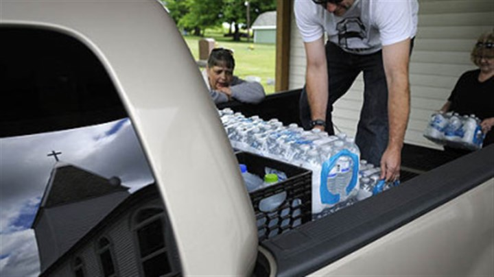 Volunteers Volunteers Jason Bell and Diane Fipe load water into a pickup truck while water delivery coordinator Janet McIntyre counts up the gallons June 4 at White Oaks Springs Presbyterian Church near Evans City.